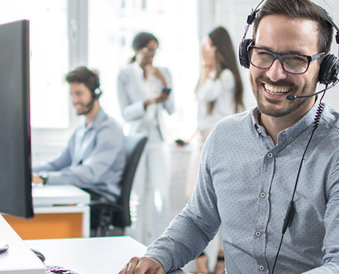 Man sitting at computer with headset on smiling