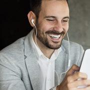 Man looking at tablet with earphones in his ears