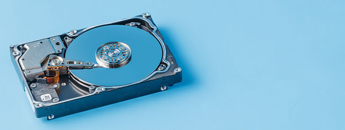 Hard drive sitting on blue backdrop representing backup options.