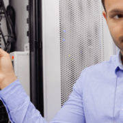 two men looking at server with lots of wires