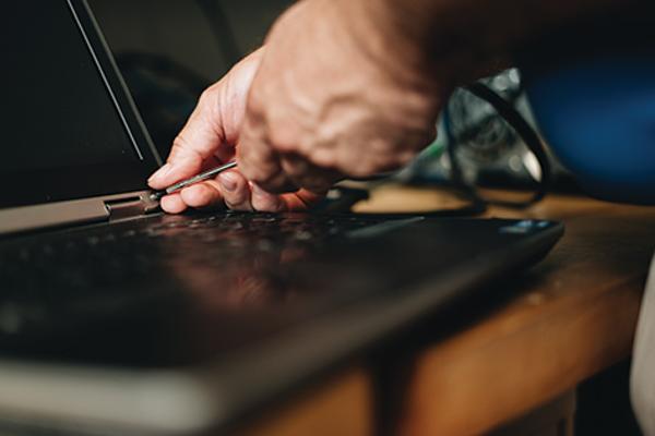 hands fixing a computer