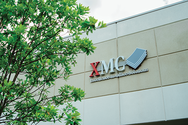 Grey exterior of building with XMC logo