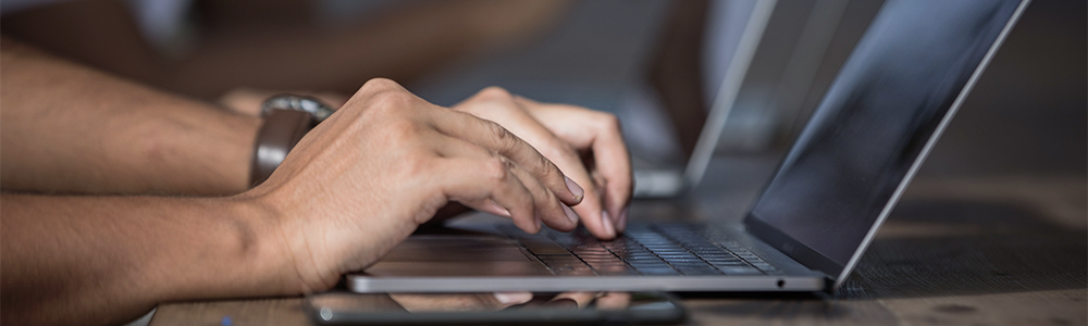 hands typing on a lap top